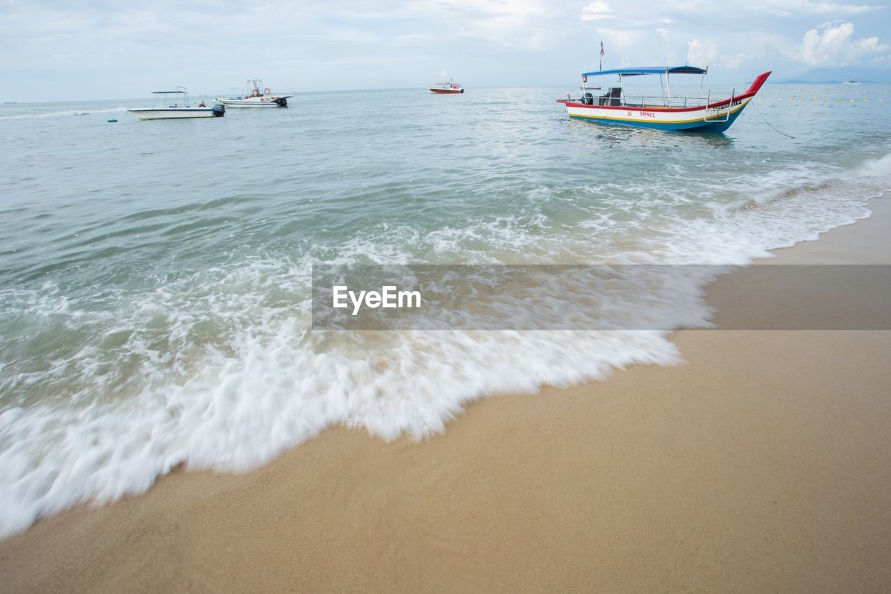 sea, water, nautical vessel, transportation, beach, mode of transportation, motion, land, wave, aquatic sport, surfing, beauty in nature, sand, day, sport, sky, nature, scenics - nature, horizon over water, anchored