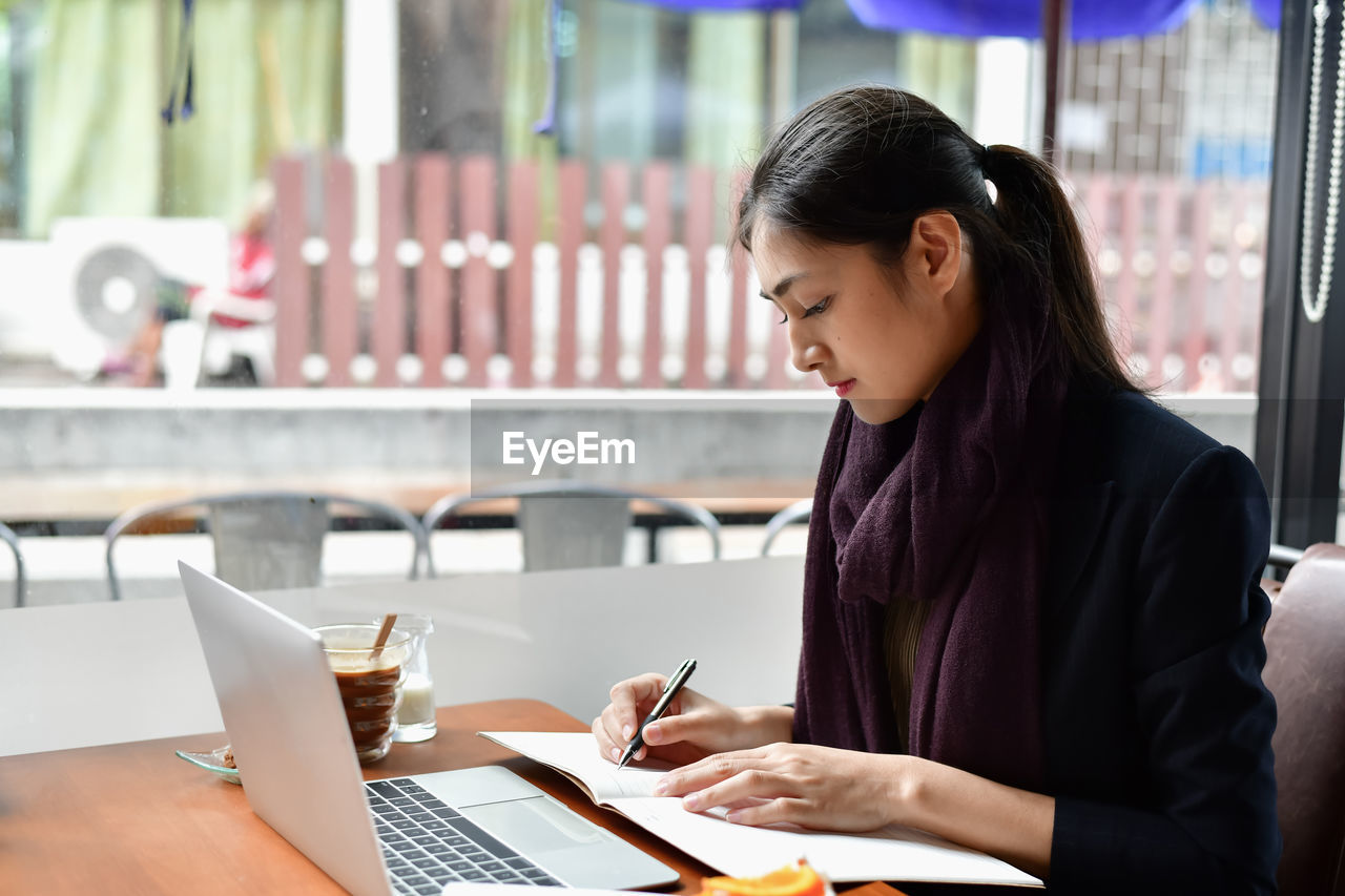 wireless technology, one person, business, table, laptop, women, technology, holding, communication, indoors, connection, adult, real people, sitting, portable information device, focus on foreground, mobile phone, computer, using laptop, glass