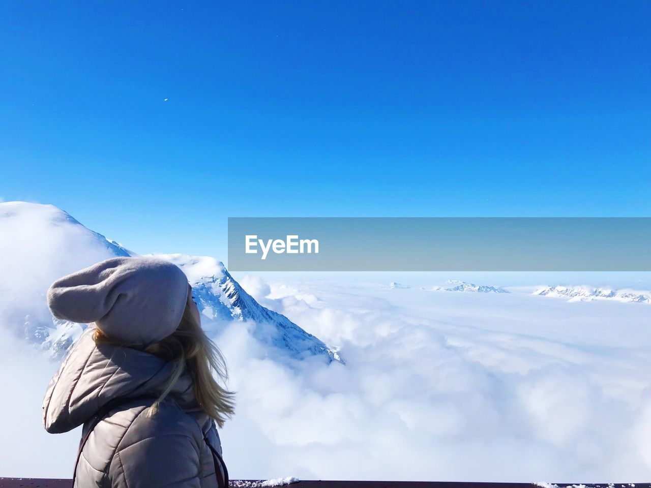 sky, winter, cold temperature, scenics - nature, beauty in nature, real people, clothing, one person, blue, day, snow, leisure activity, cloud - sky, nature, warm clothing, lifestyles, tranquil scene, copy space, hat, outdoors, snowcapped mountain
