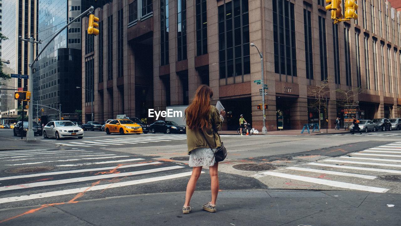 Rear View Of Female Standing On Sidewalk