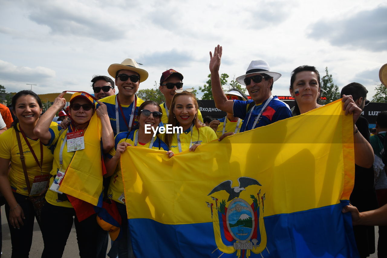 group of people, real people, women, men, happiness, day, females, smiling, lifestyles, people, emotion, flag, adult, crowd, standing, yellow, leisure activity, portrait, looking at camera, outdoors