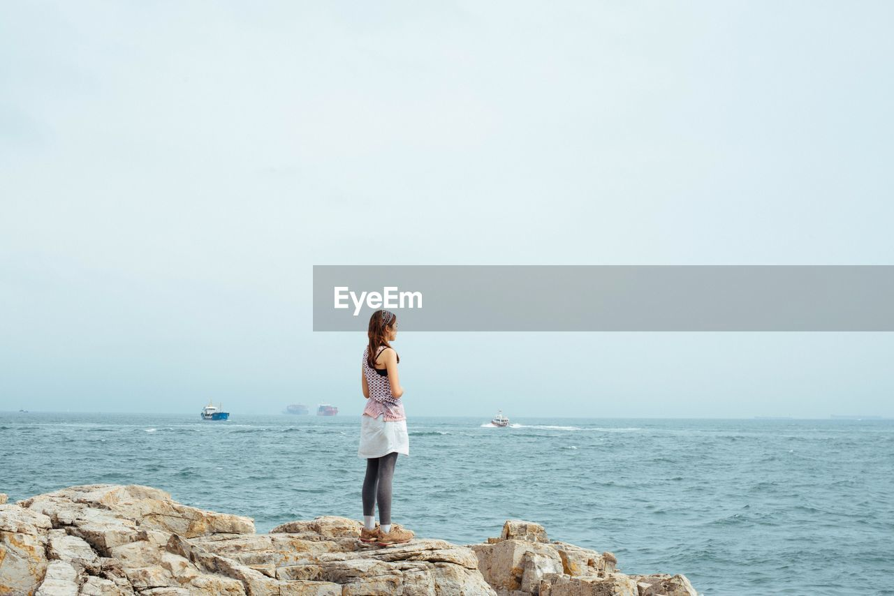Rear View Of Woman Overlooking Calm Sea