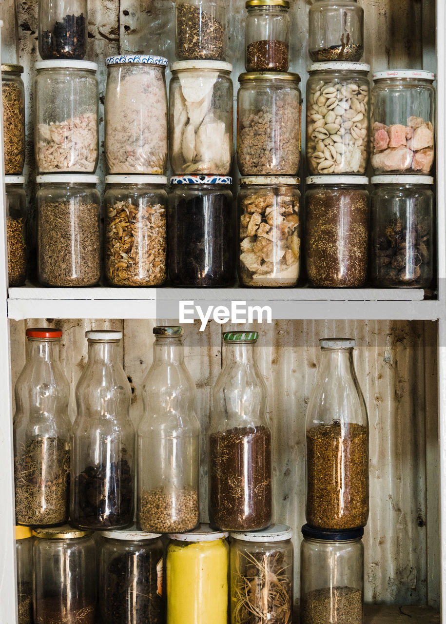 container, bottle, shelf, choice, indoors, glass - material, large group of objects, variation, food and drink, jar, transparent, no people, in a row, order, abundance, side by side, retail, arrangement, food, close-up, herb