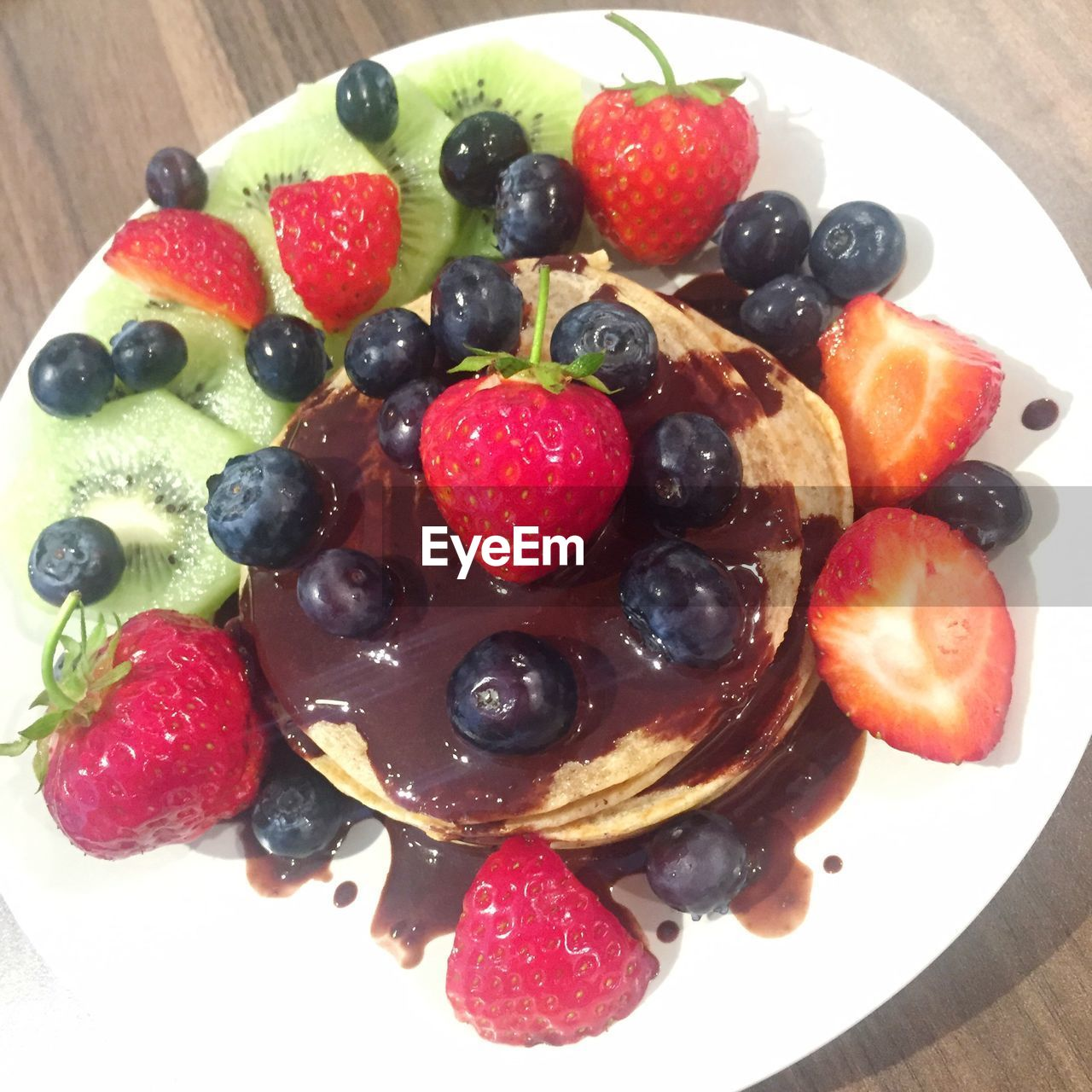 Directly above shot of pancake garnished with fruits in plate on table