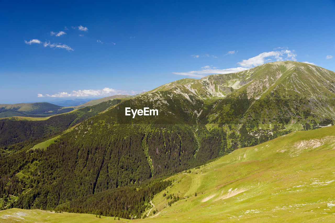 Scenic View Of Green Mountains Against Blue Sky