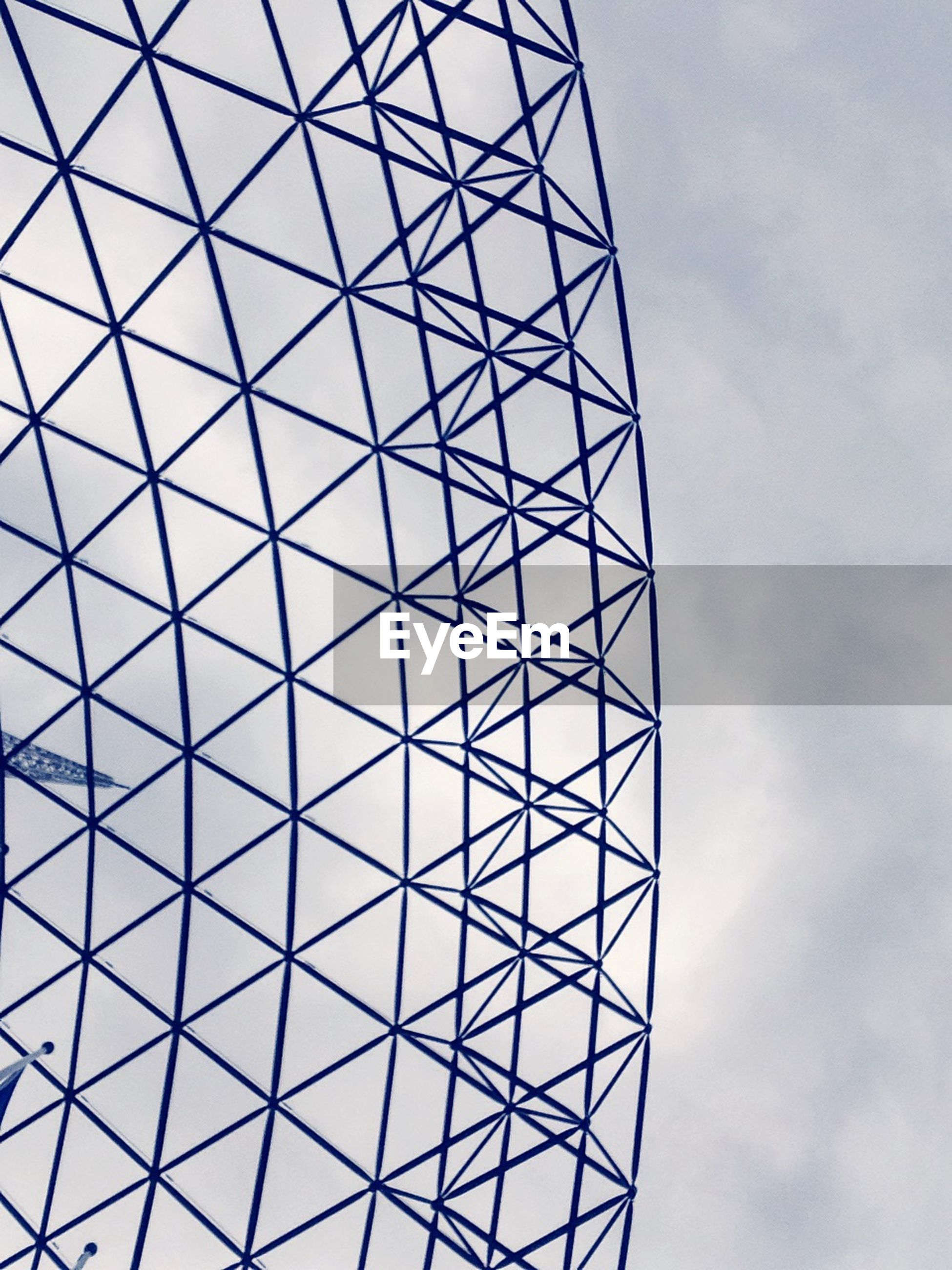 low angle view, built structure, sky, architecture, pattern, tall - high, tower, grid, full frame, cloud - sky, directly below, backgrounds, glass - material, modern, geometric shape, day, design, metal, no people, architectural feature