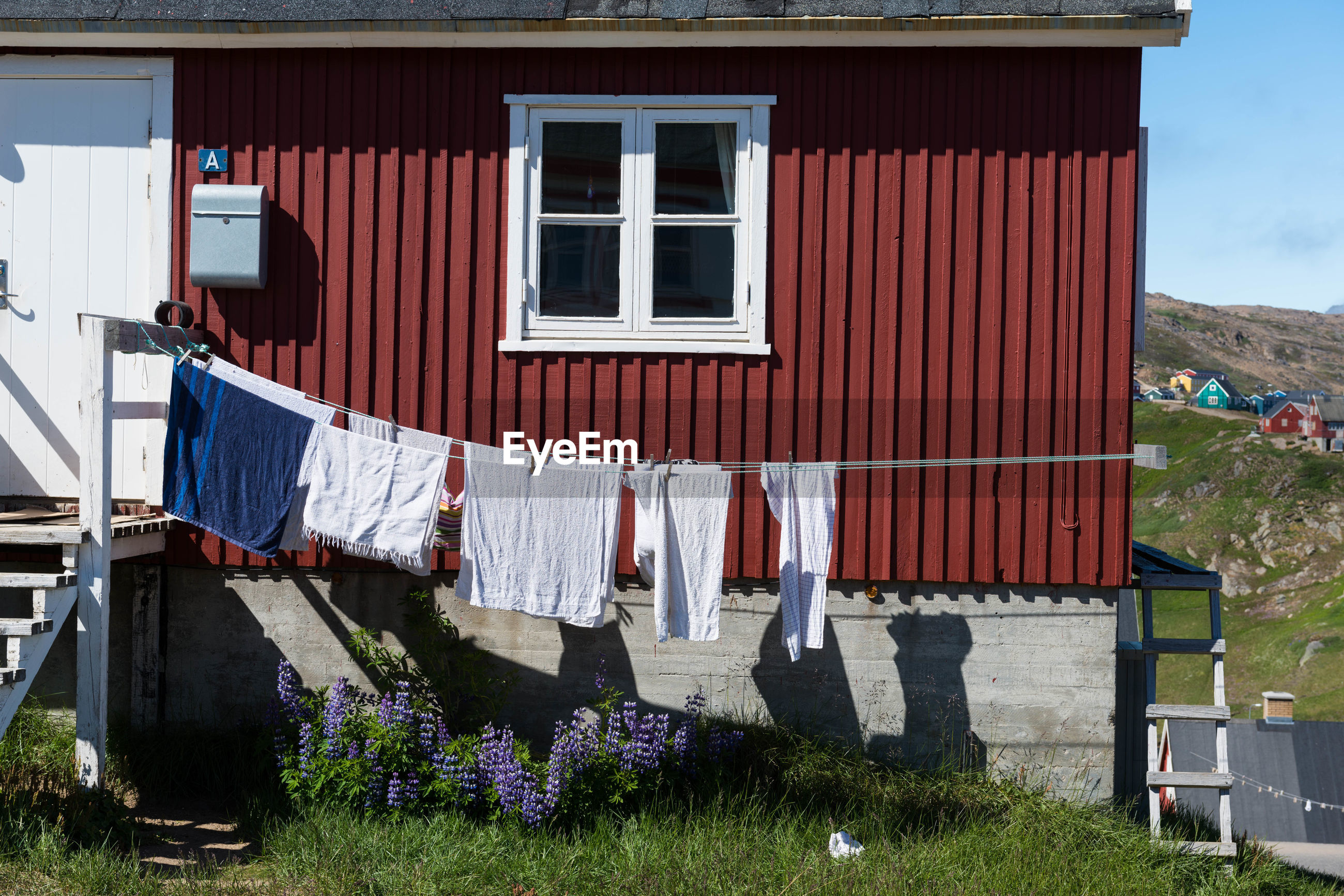 CLOTHES DRYING ON HOUSE AGAINST SKY