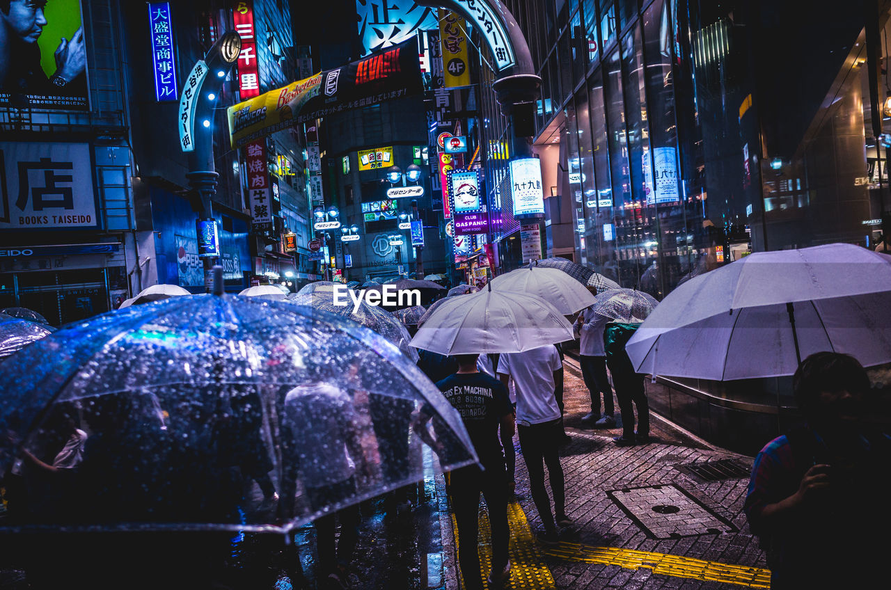 People Holding Umbrellas While Walking On Street Amidst Buildings At Night