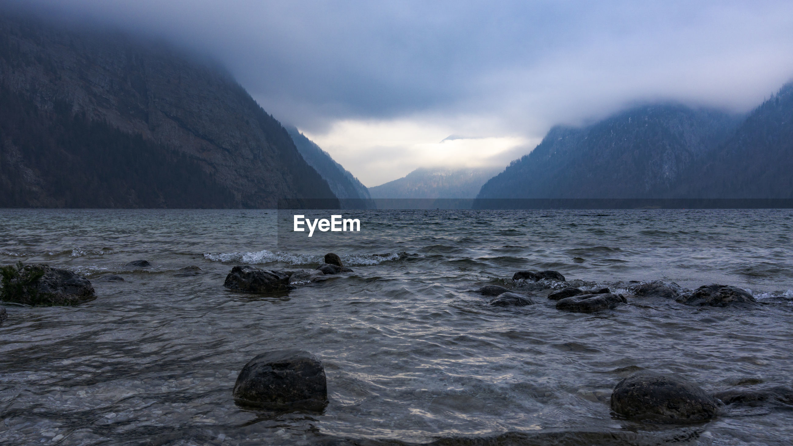 SCENIC VIEW OF ROCKS IN SEA AGAINST MOUNTAINS