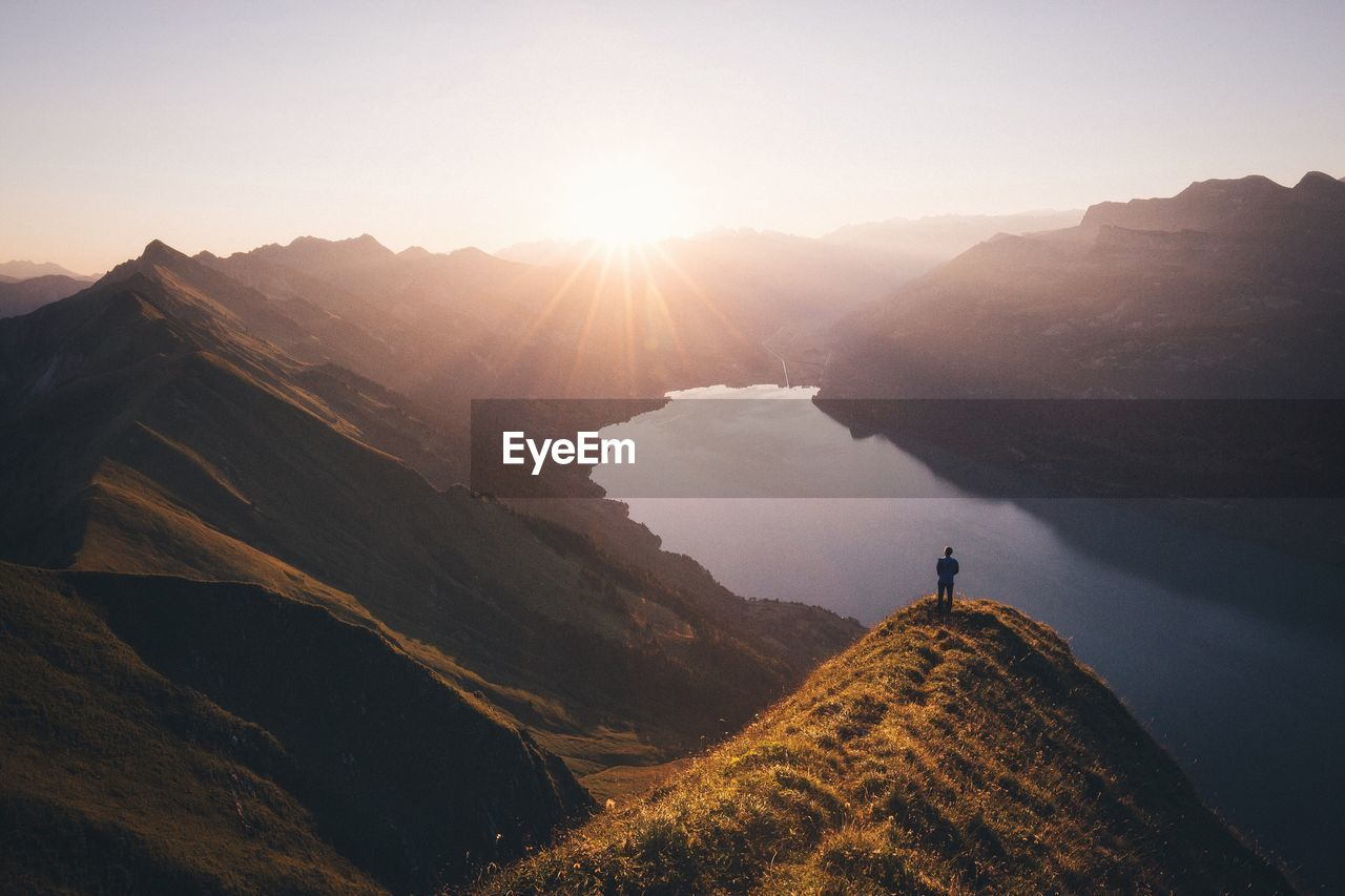 Man Standing On Cliff Looking Down On Mountain Lake