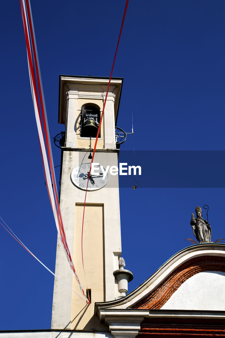 Low angle view of clock tower with ribbons against clear sky