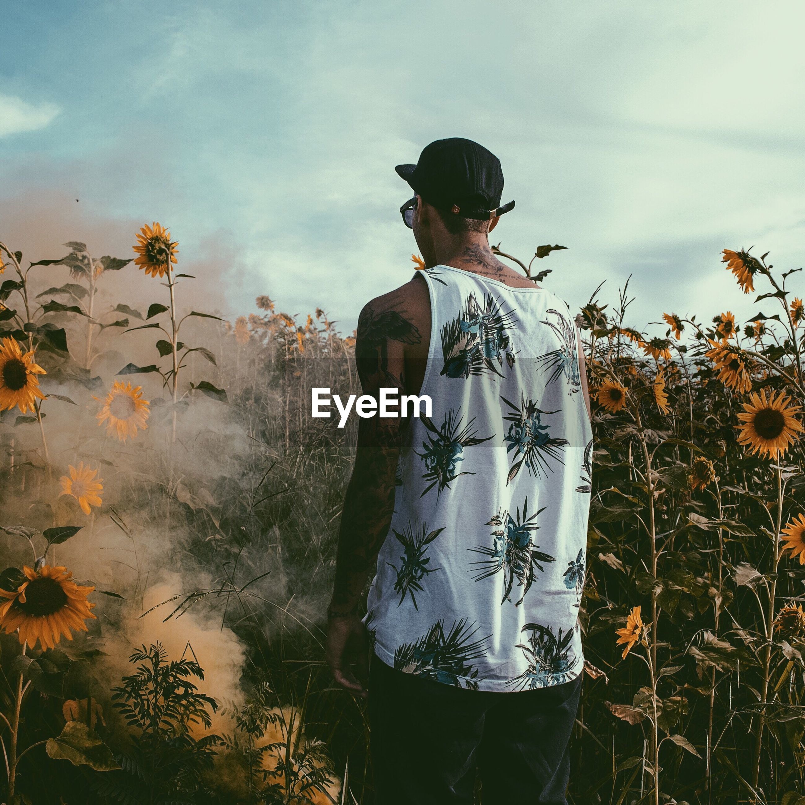 Rear view of man standing by smoke on sunflower field against sky