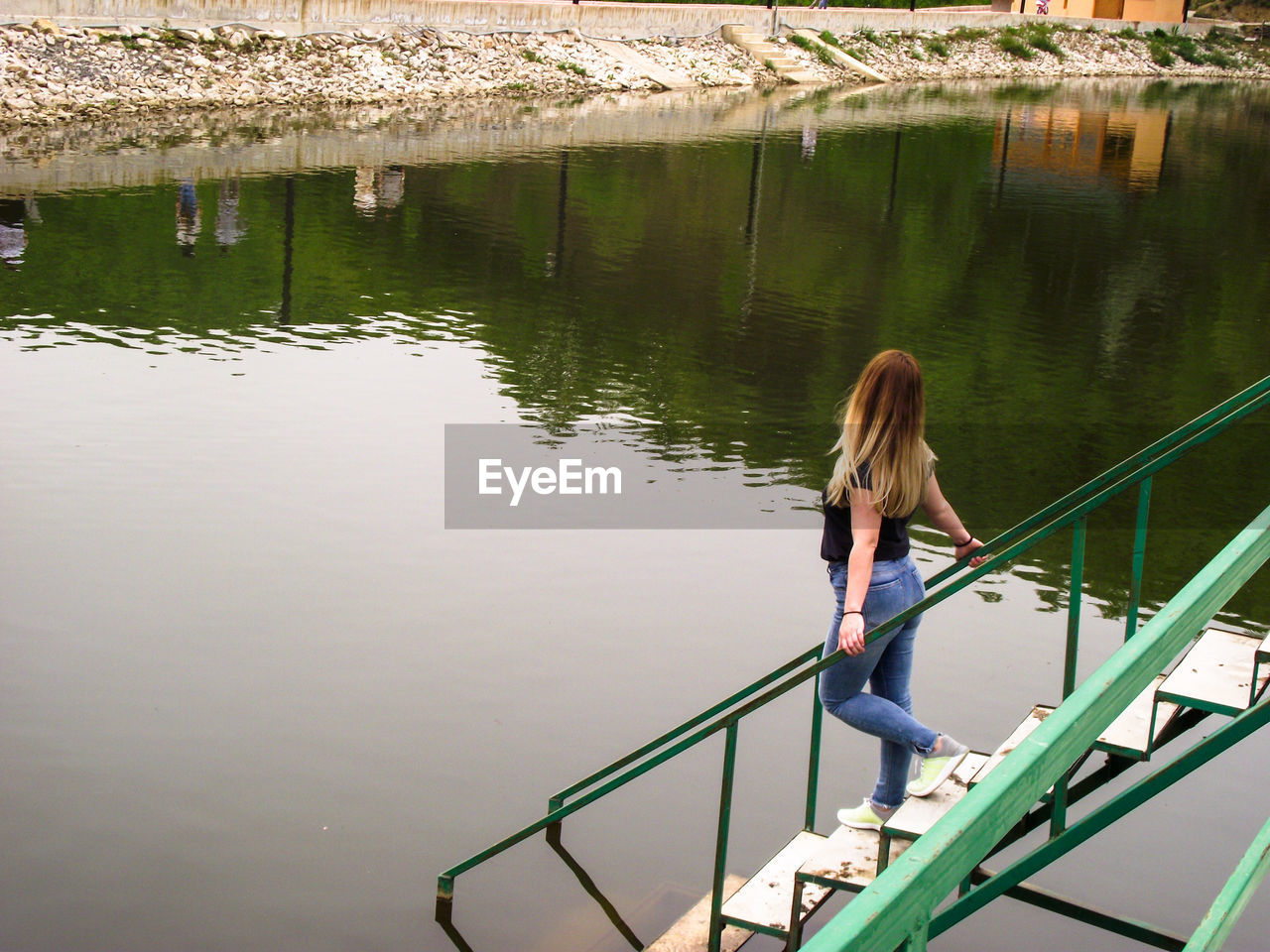 Woman standing on steps over lake