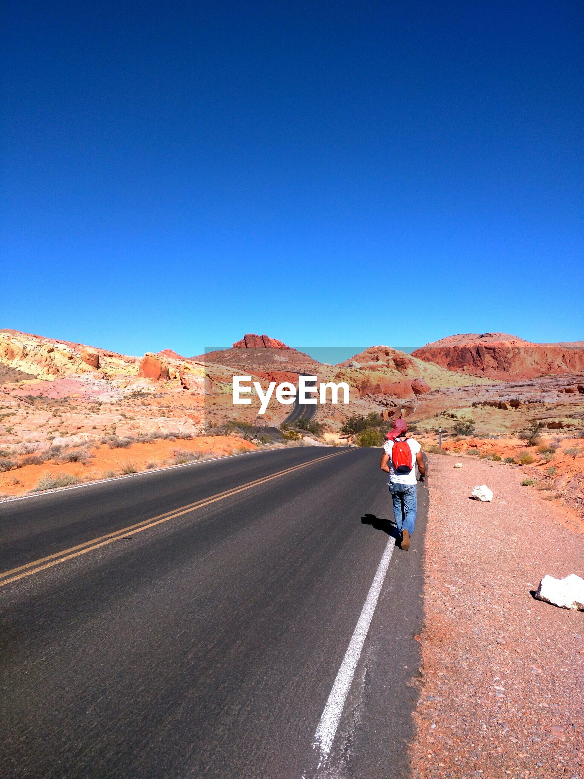 Rear view of man on road amidst desert against clear blue sky