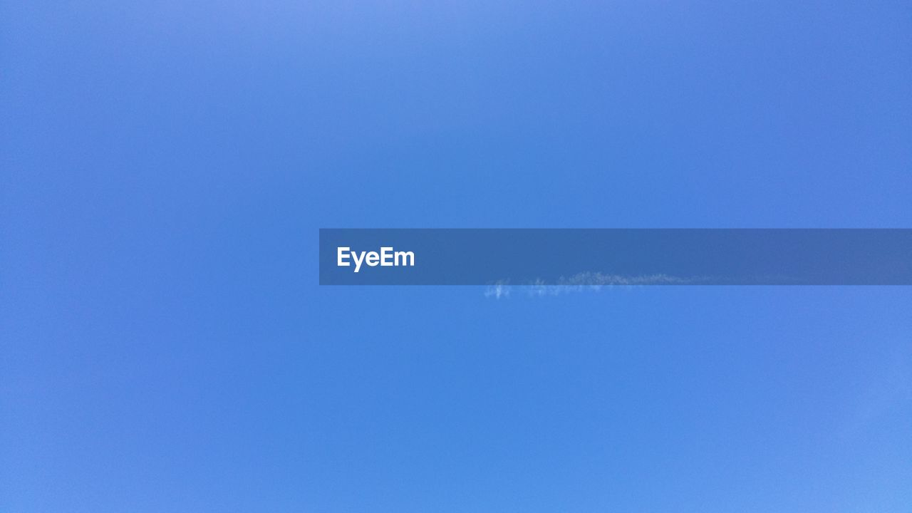 blue, low angle view, sky, no people, nature, day, sky only, beauty in nature, outdoors, clear sky, vapor trail, flying, contrail, bird