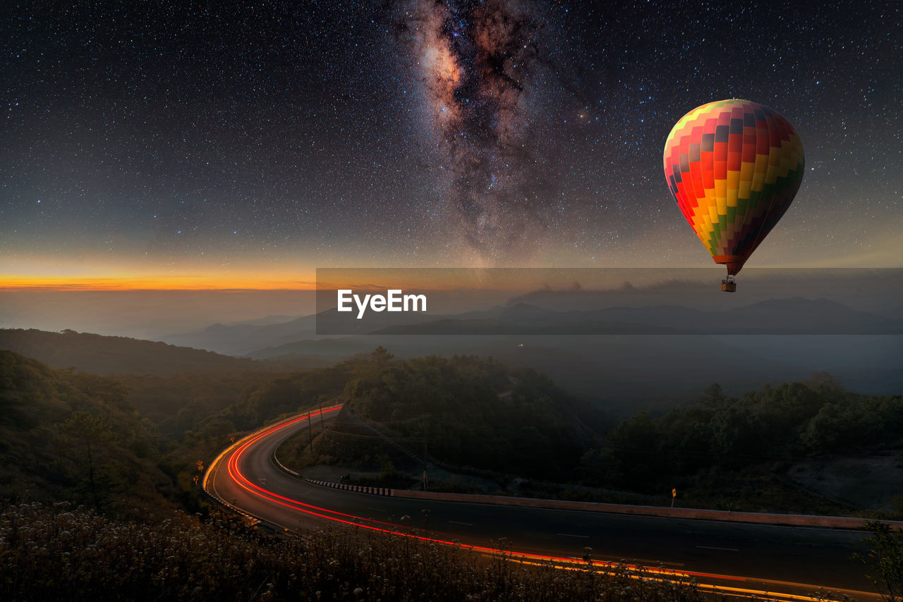 Hot Air Balloon Flying Over Landscape Against Dramatic Sky At Night