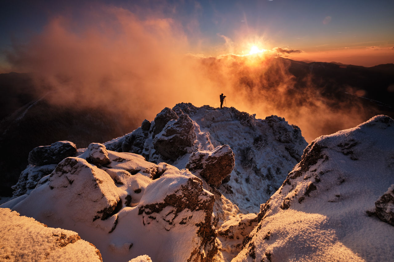 Scenic view of man standing on snowcapped mountains against sky during sunset