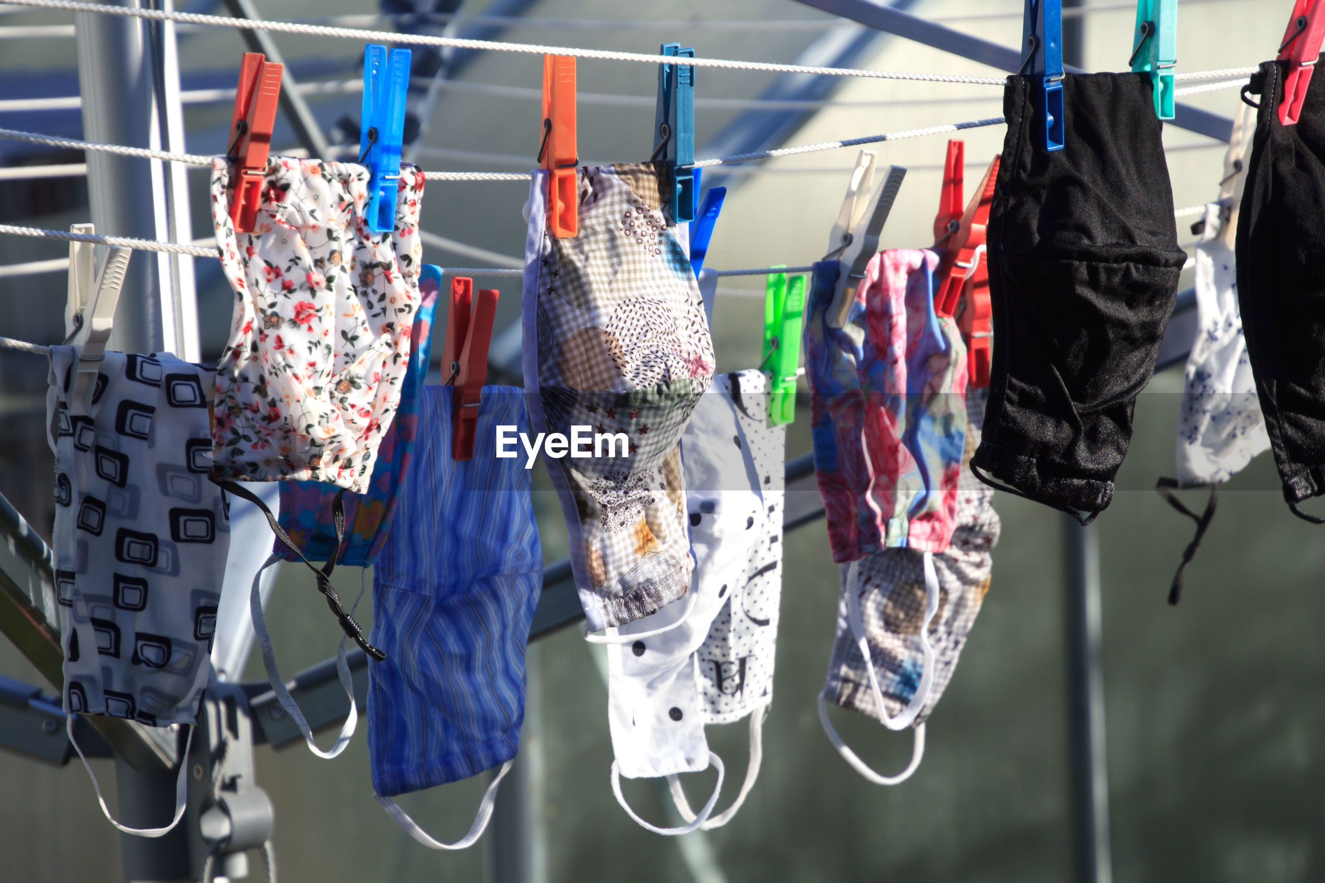CLOSE-UP OF MULTI COLORED CLOTHESPINS HANGING ON RACK
