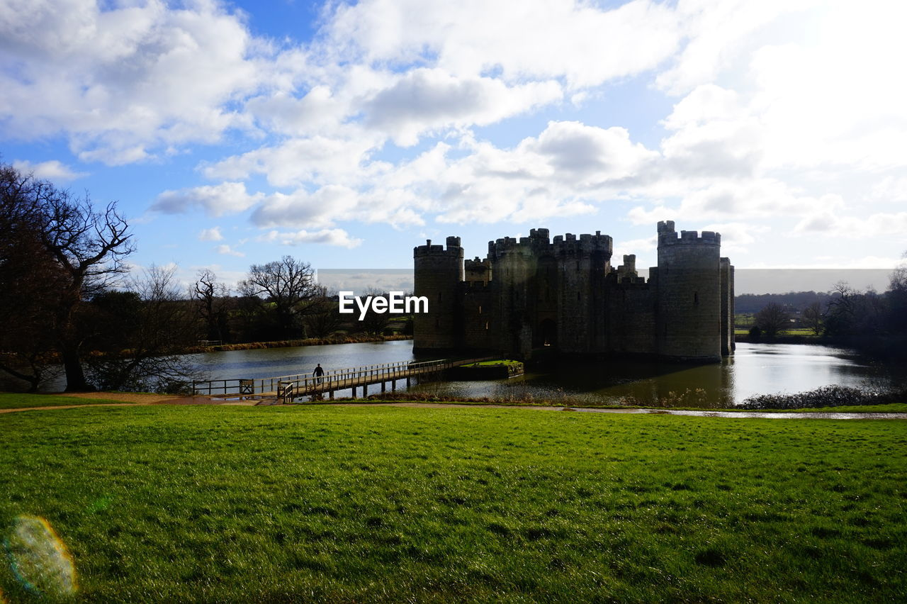 water, architecture, sky, cloud - sky, river, grass, built structure, building exterior, history, nature, castle, tree, outdoors, day, no people, bridge - man made structure, scenics, beauty in nature