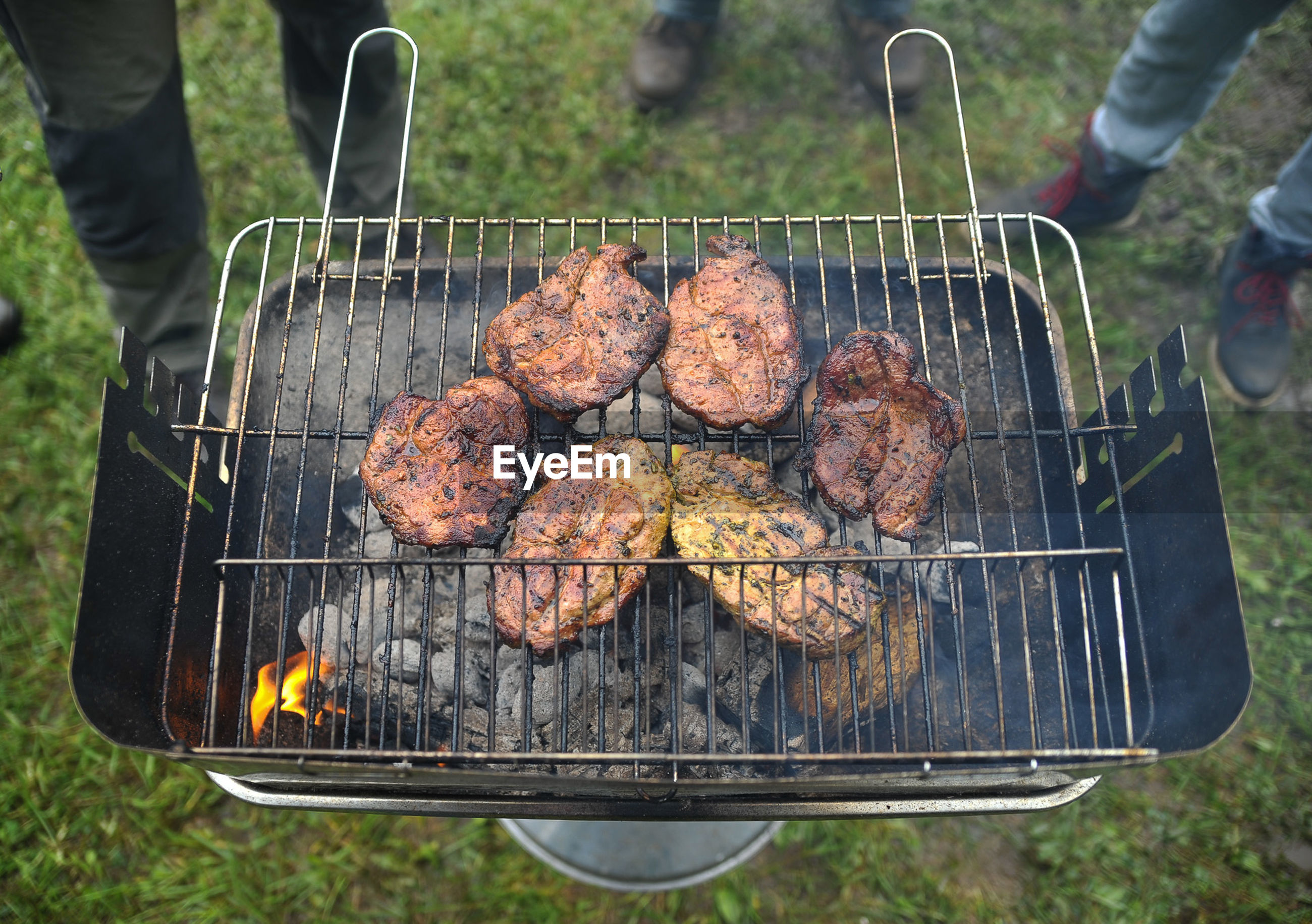 High angle view of meat cooking on barbecue grill at yard