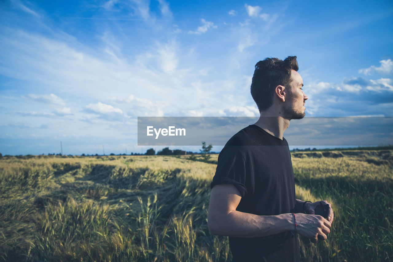 Side View Of Young Man With Eyes Closed While Standing On Wheat Field Against Sky