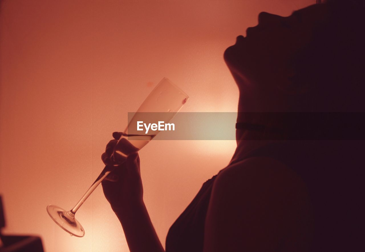 Side view of woman holding champagne flute in illuminated room