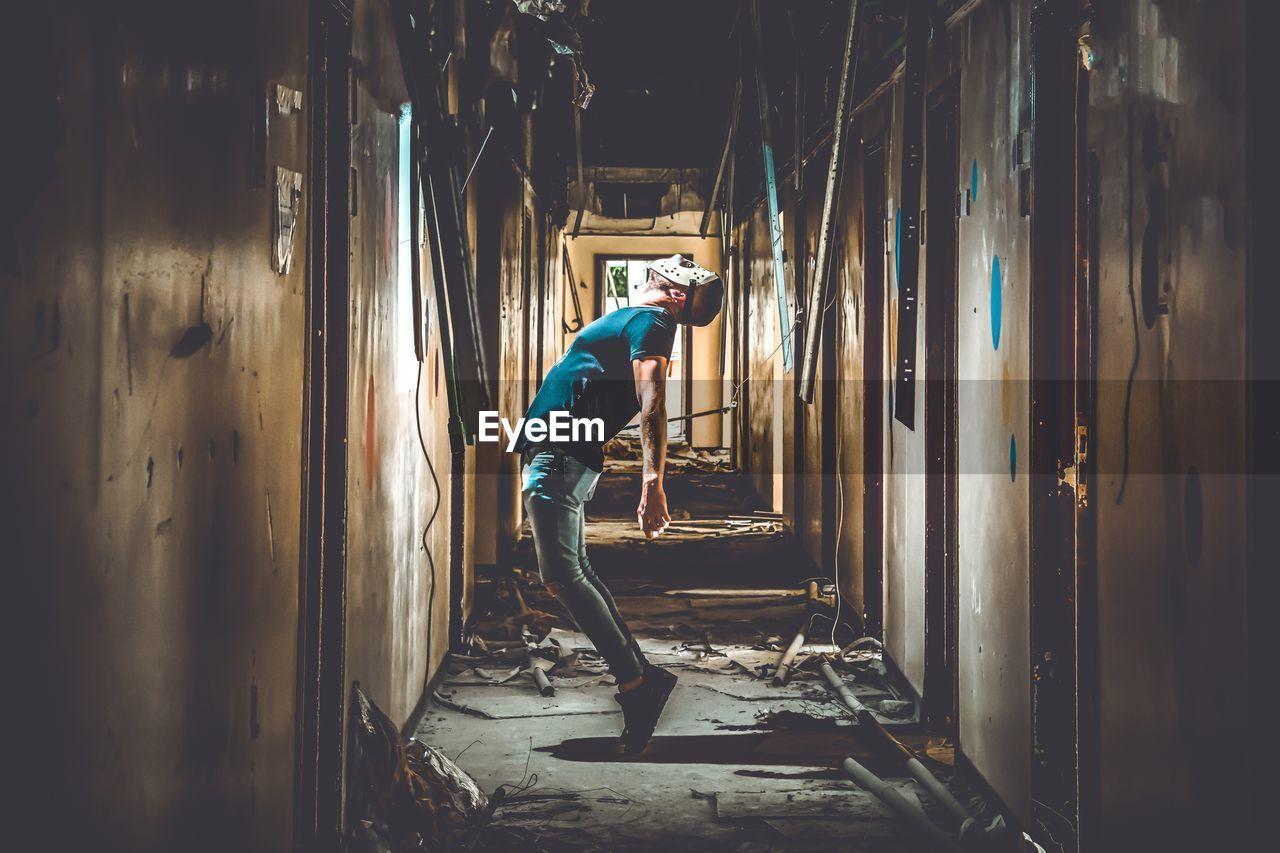 Man In Mask Standing In Corridor