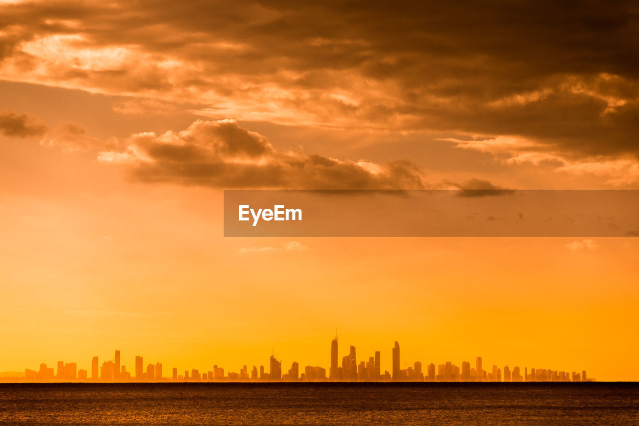 Distant View Of City By Sea Against Orange Sky