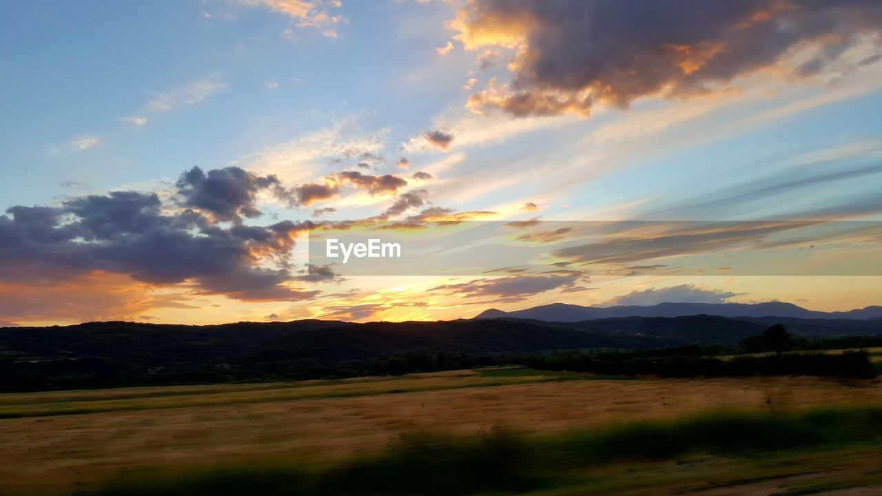 sunset, scenics, beauty in nature, nature, tranquil scene, mountain, tranquility, landscape, sky, cloud - sky, no people, outdoors, mountain range, silhouette, rural scene, day