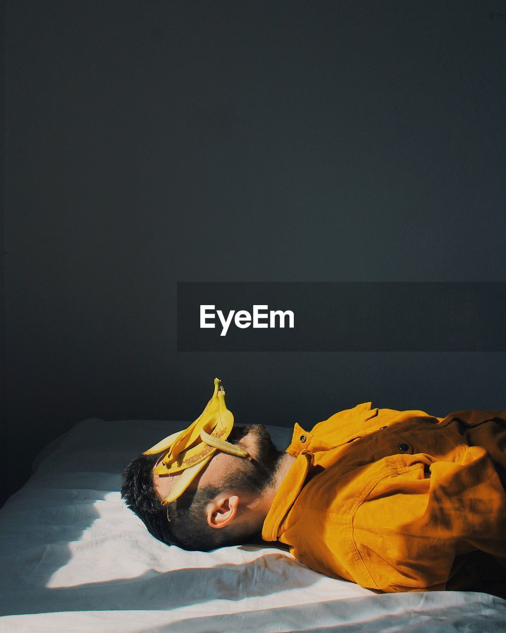 copy space, one person, indoors, lying down, studio shot, eyes closed, relaxation, bed, sleeping, young adult, real people, young men, furniture, men, front view, domestic room, black background, yellow, contemplation
