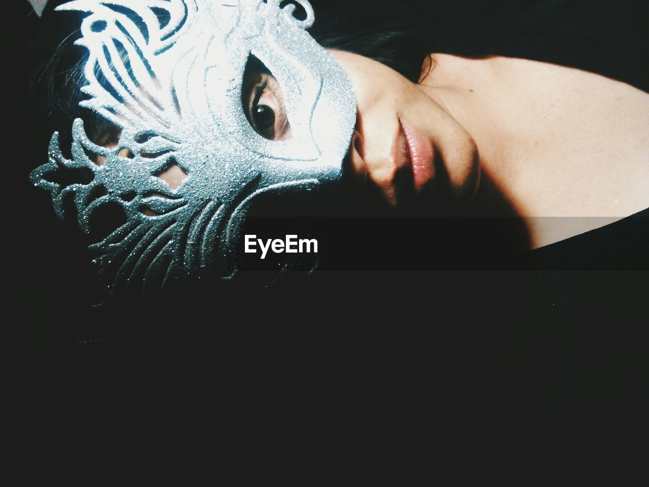 High Angle View Of Woman Wearing Carnival Eye Mask Against Black Background