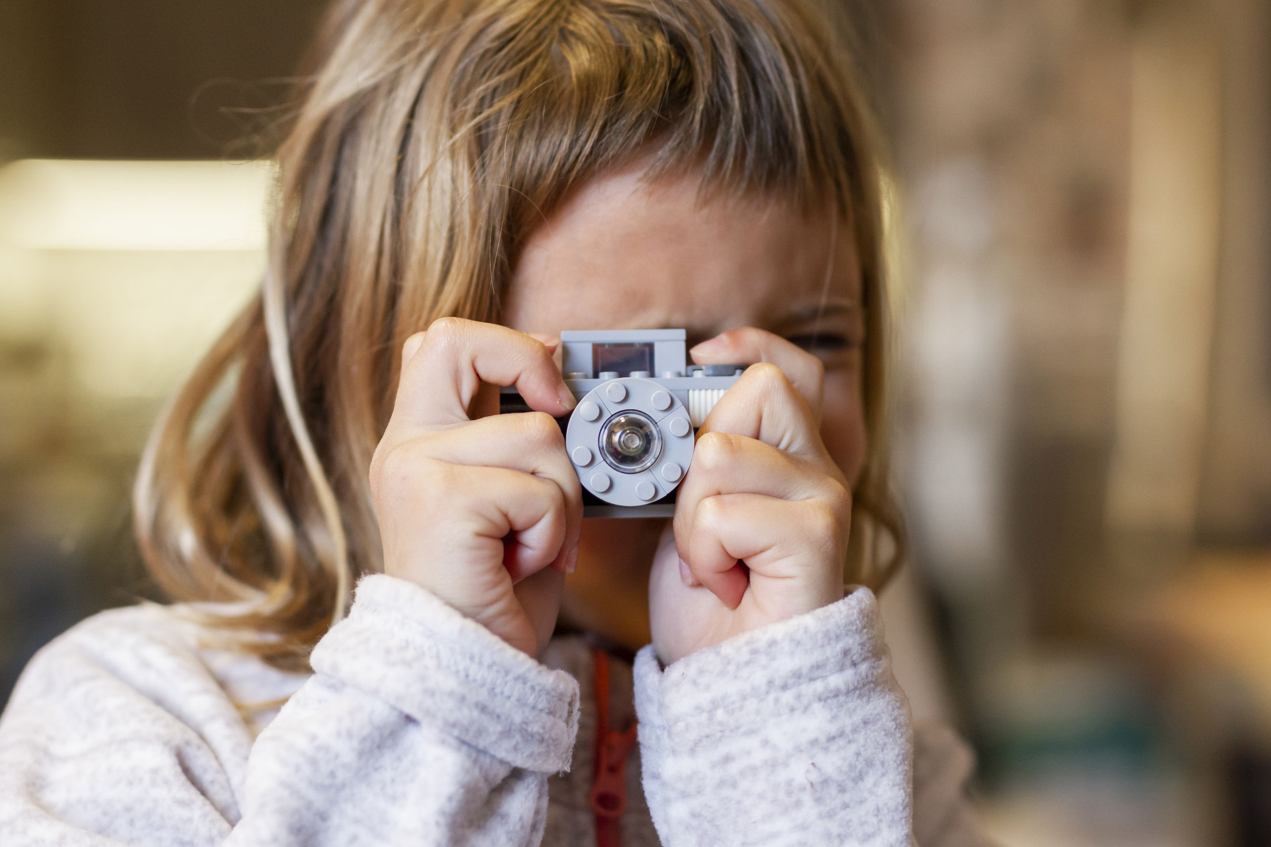 CLOSE-UP PORTRAIT OF BOY WITH CAMERA