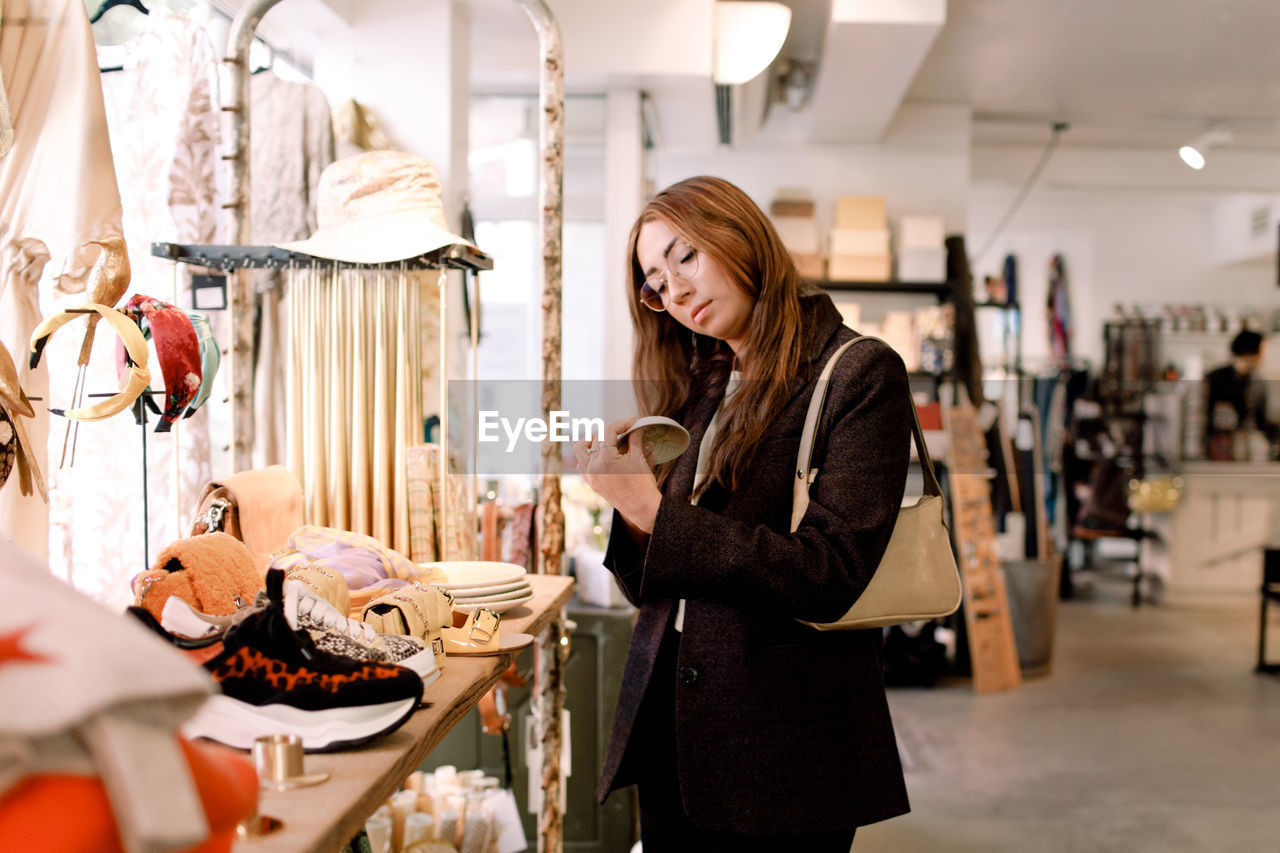 SIDE VIEW OF A YOUNG WOMAN HOLDING A STORE