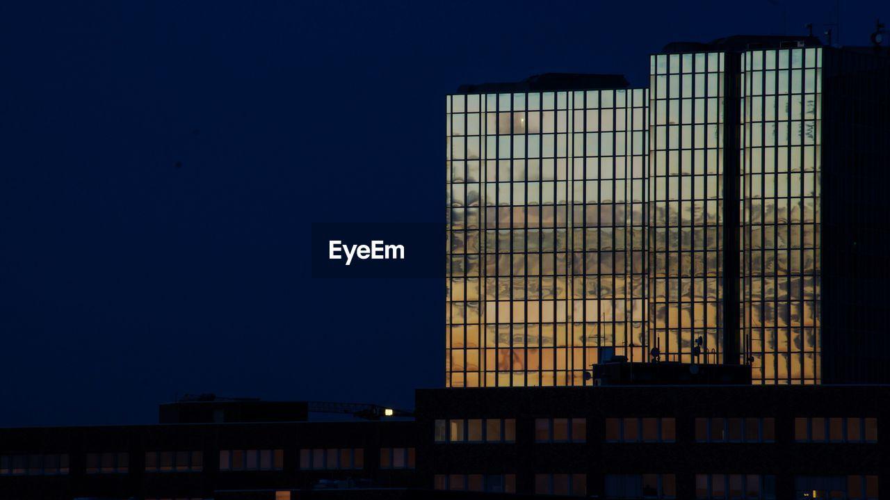 Modern buildings against sky in city at night
