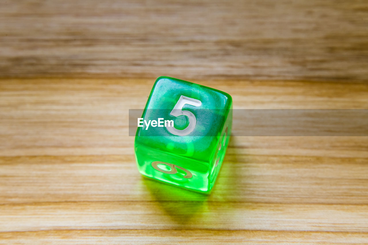 green color, wood - material, indoors, table, no people, still life, close-up, toy block, single object, wood grain, text, high angle view, toy, wood, copy space, number, finance, block, multi colored, education