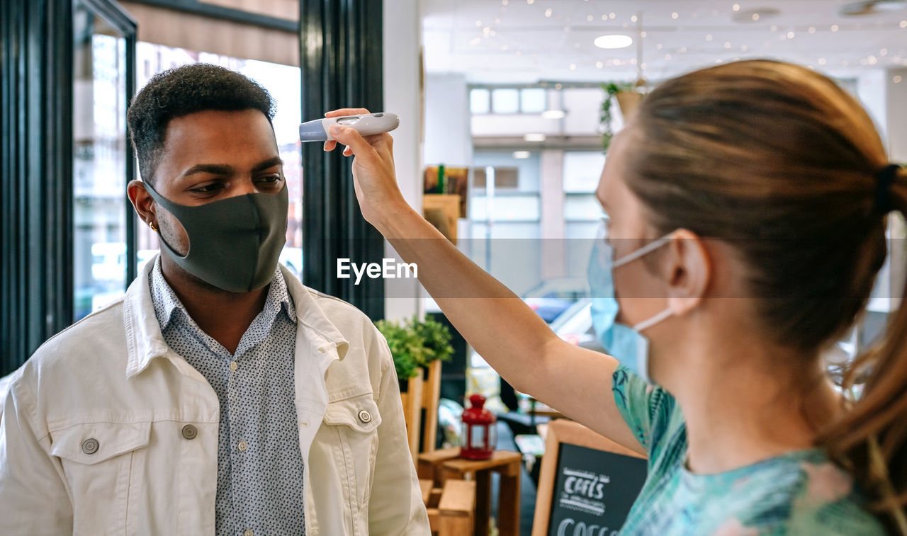 Woman checking temperature of customers wearing mask in restaurant
