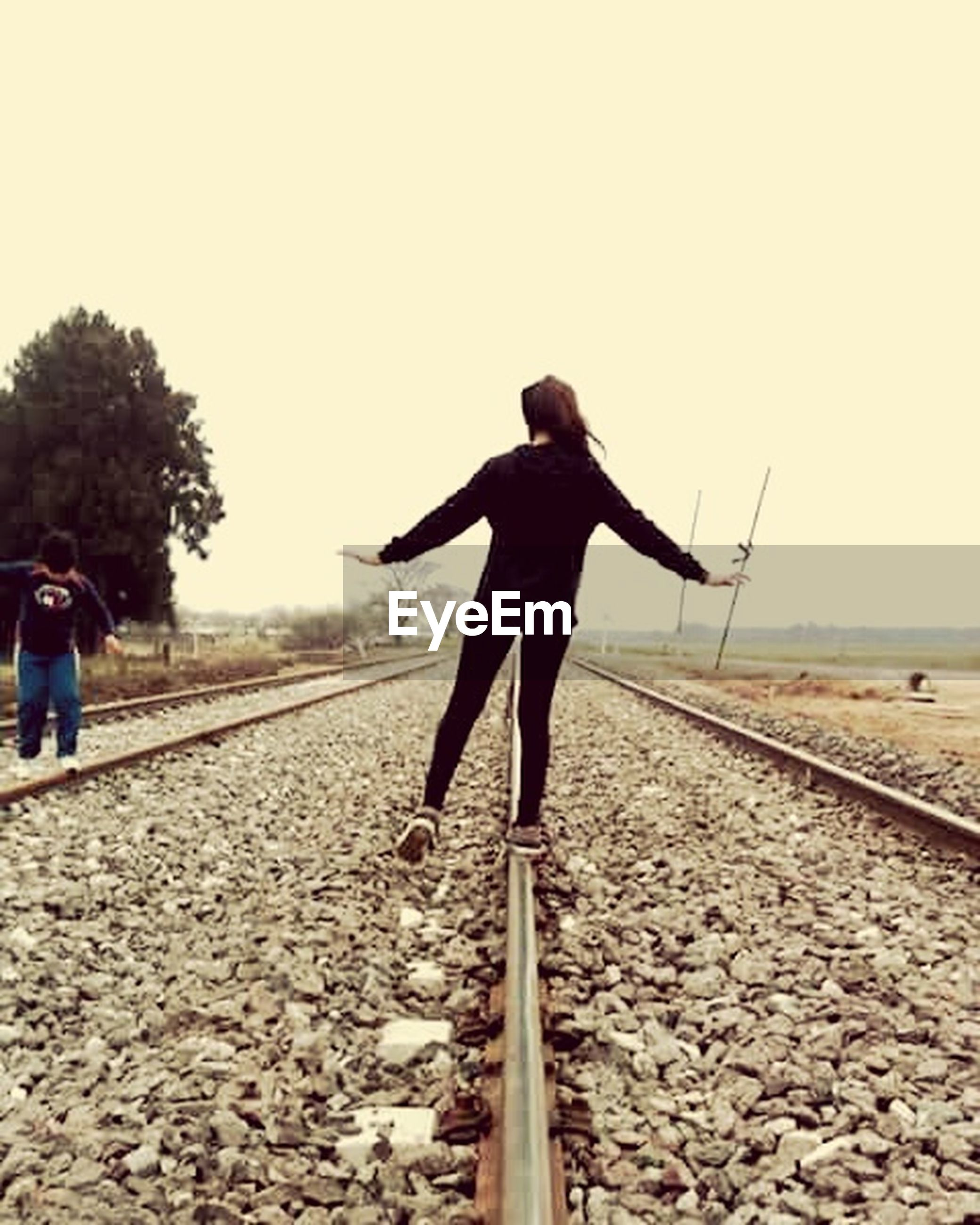 full length, lifestyles, rear view, leisure activity, clear sky, casual clothing, standing, walking, railroad track, men, the way forward, sky, person, copy space, day, landscape, outdoors, nature