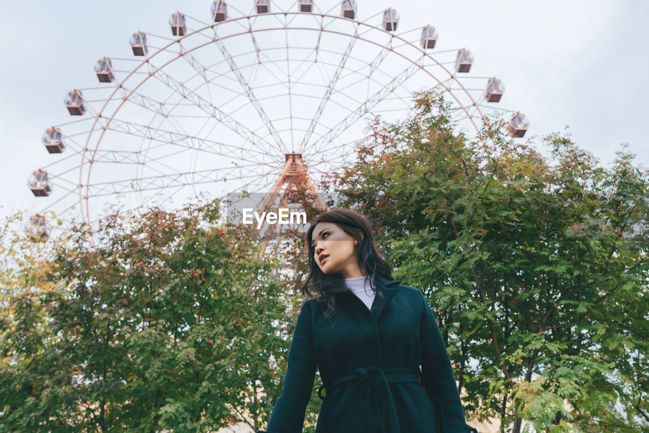 LOW ANGLE VIEW OF WOMAN STANDING IN PARK AGAINST SKY