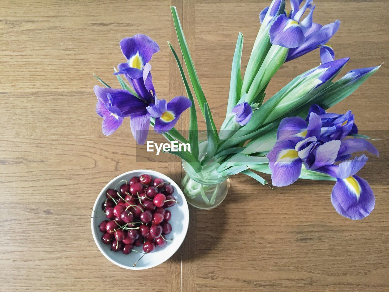 High Angle View Of Iris Flowers In Vase By Cherries On Table