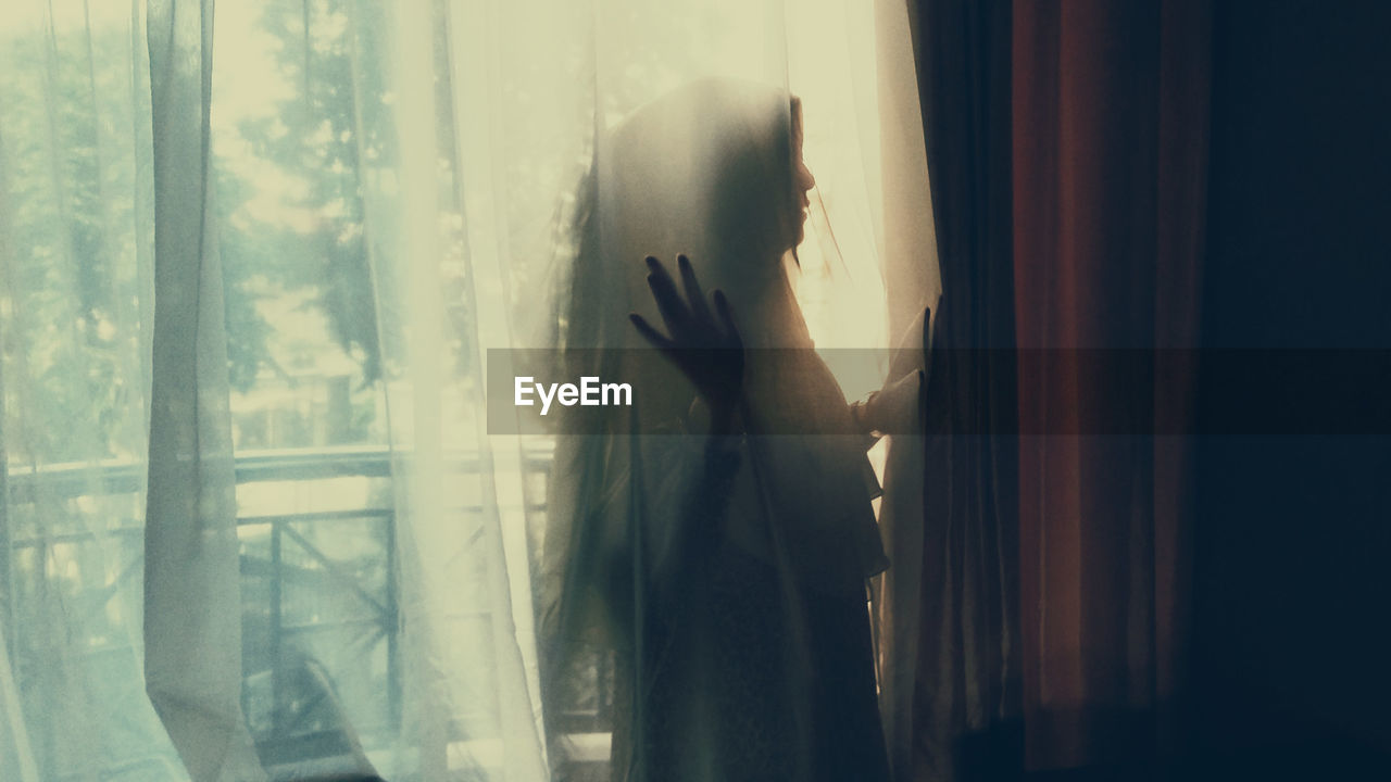 window, one person, curtain, women, indoors, real people, standing, lifestyles, glass - material, transparent, adult, day, waist up, side view, home interior, human hand, textile, three quarter length, hand, depression - sadness