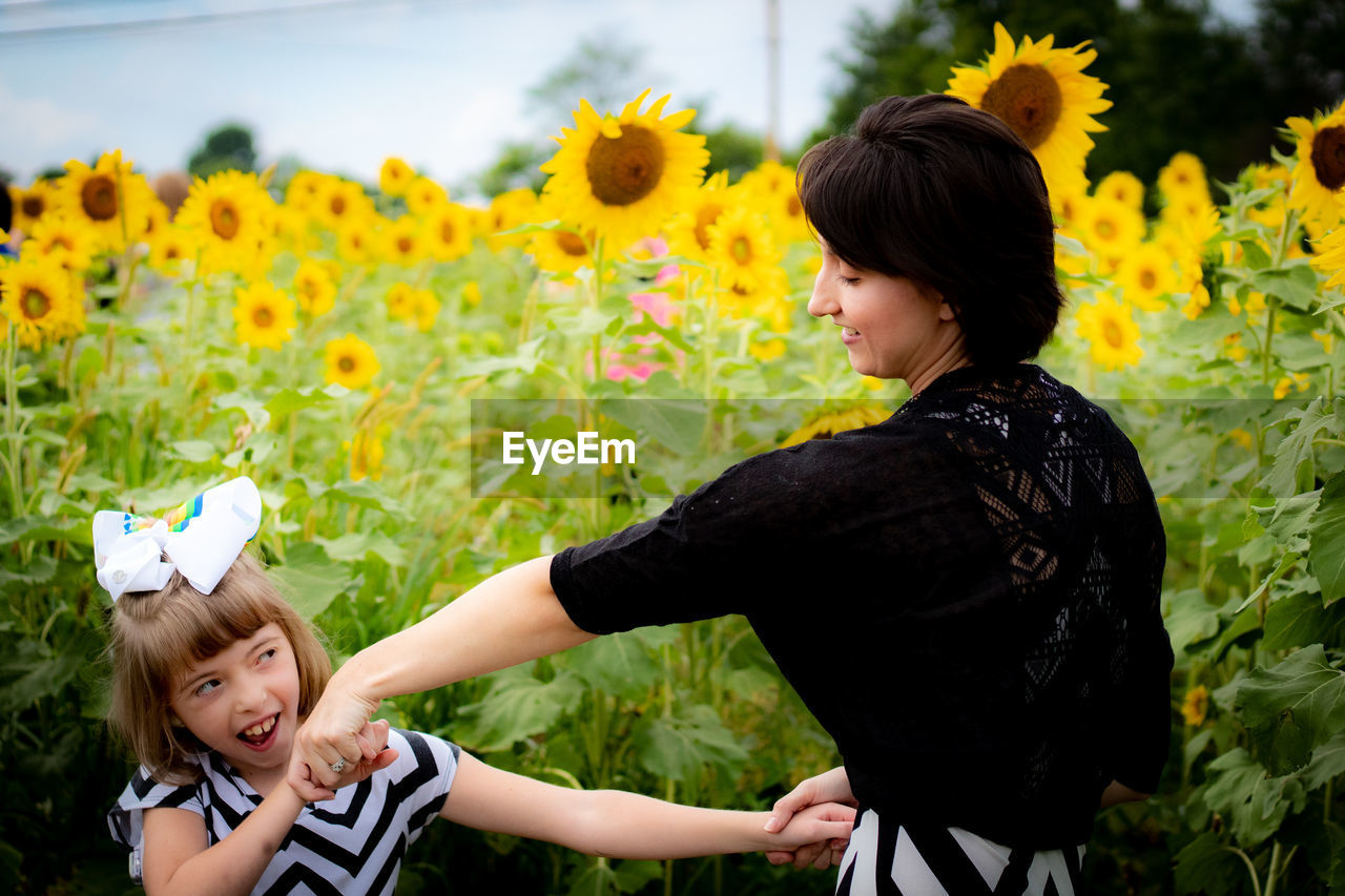 Happy Mother And Daughter Dancing On Sunflower Field