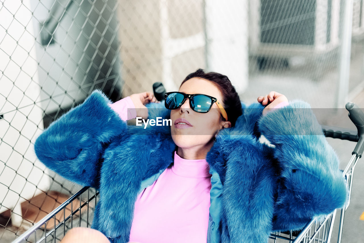 one person, real people, lifestyles, glasses, leisure activity, front view, sunglasses, day, fashion, focus on foreground, portrait, blue, architecture, standing, security, casual clothing, clothing, outdoors, warm clothing, hairstyle