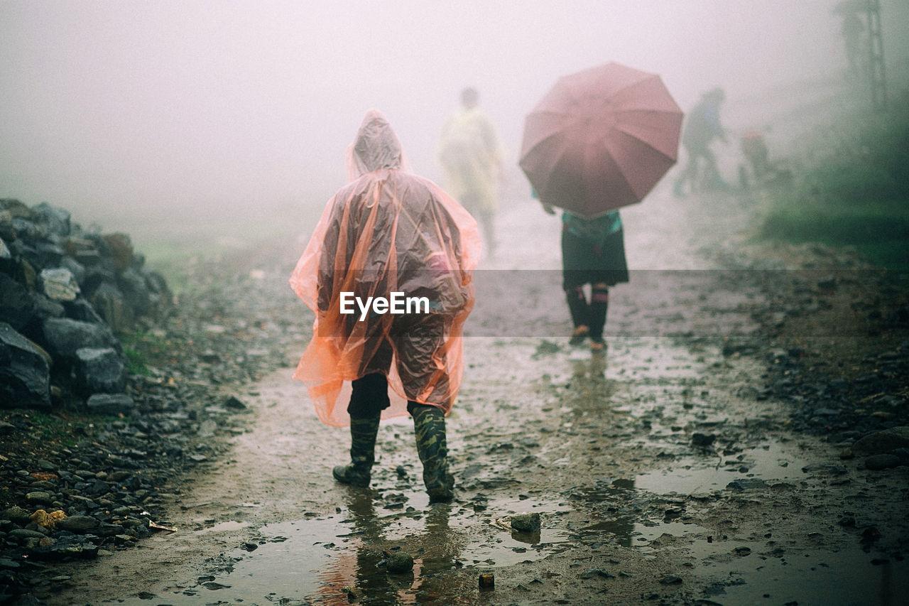 Rear view of people walking in rain