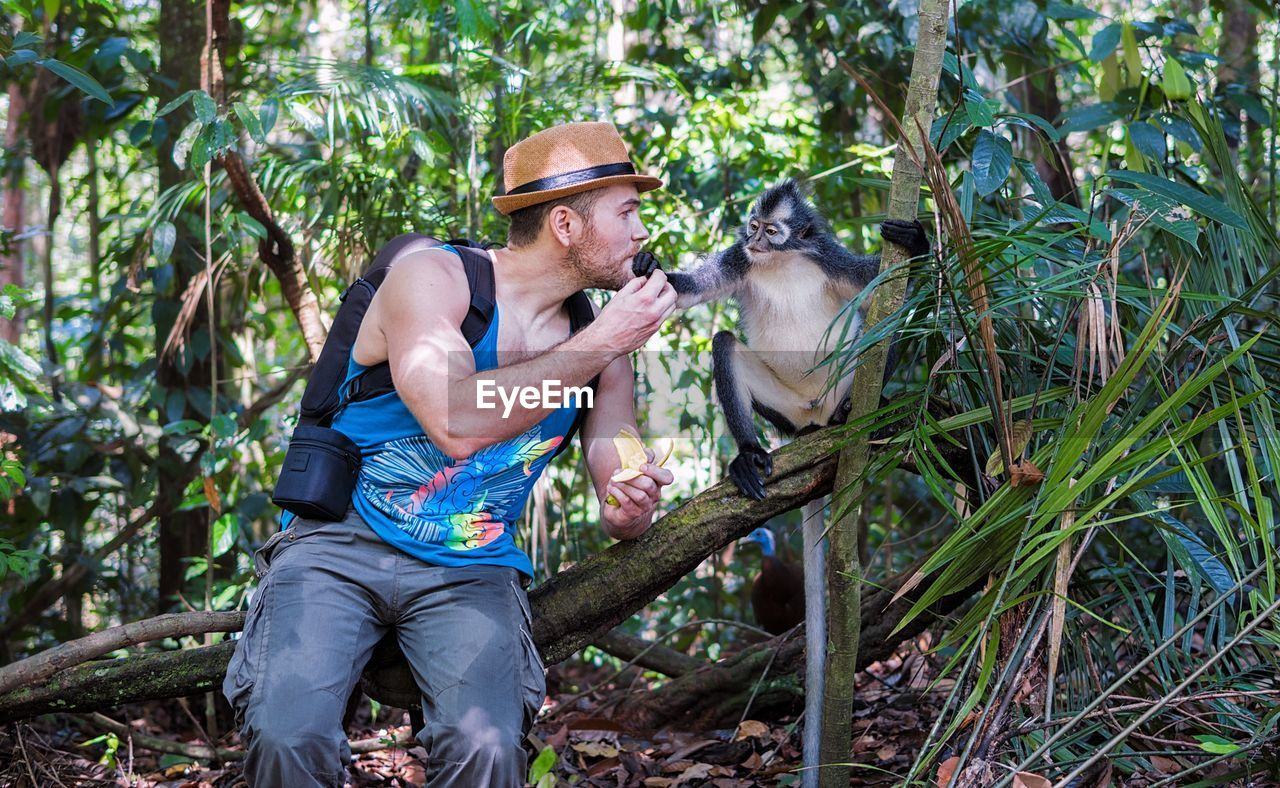 one person, one animal, outdoors, mature adult, mammal, tree, casual clothing, forest, nature, dog, leisure activity, senior adult, eyeglasses, pets, day, real people, smiling, animal wildlife, one man only, food, domestic animals, happiness, men, only men, people, adults only, adult