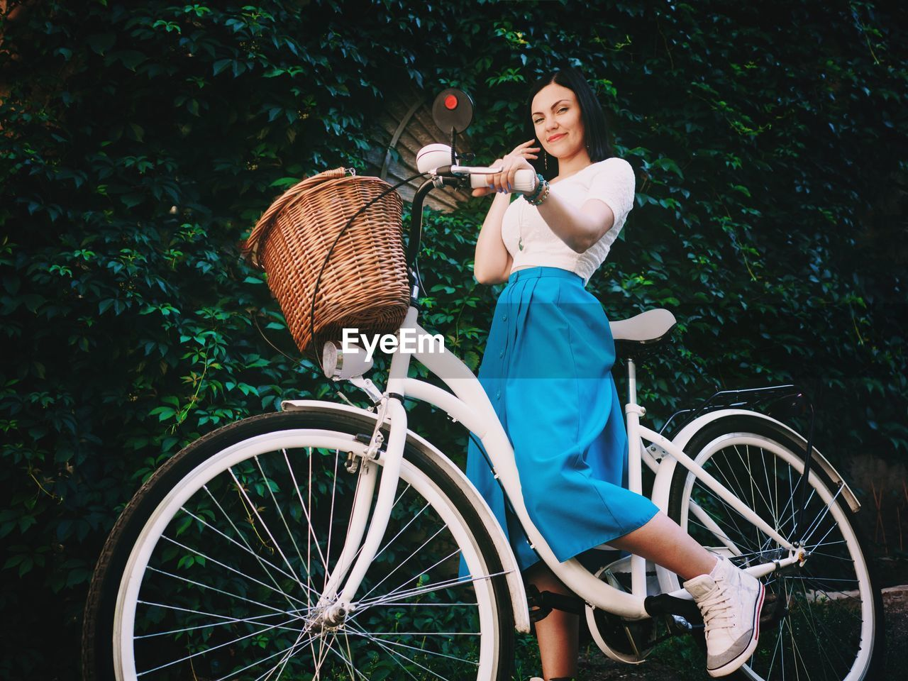 Low angle portrait of beautiful woman with bicycle against ivy