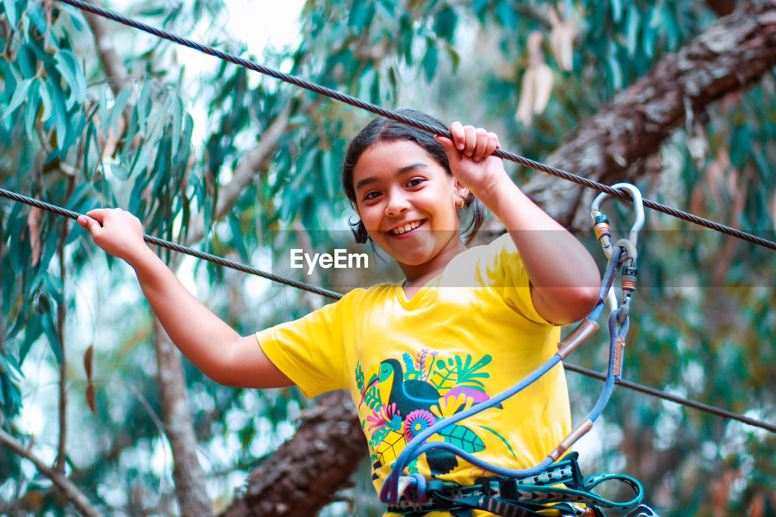 Portrait of smiling girl holding rope against trees