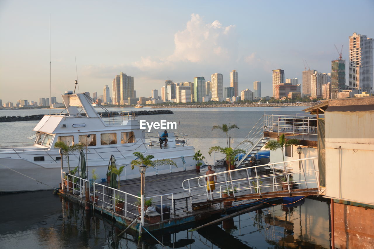 architecture, built structure, building exterior, water, sky, nautical vessel, city, transportation, sea, nature, mode of transportation, building, waterfront, cloud - sky, no people, office building exterior, moored, outdoors, day, cityscape, skyscraper, cruise ship, yacht