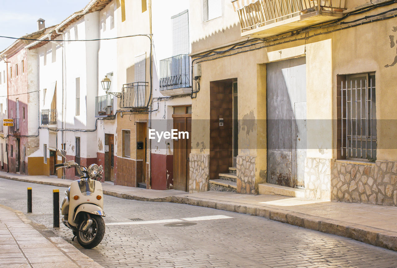 architecture, building exterior, built structure, transportation, mode of transportation, city, building, land vehicle, street, residential district, day, scooter, motor scooter, motorcycle, road, outdoors, sunlight, no people, house