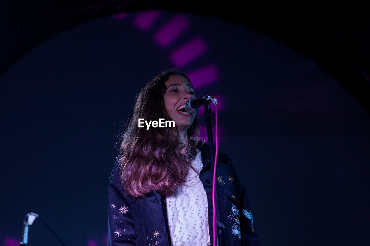 Low angle view of woman singing during concert