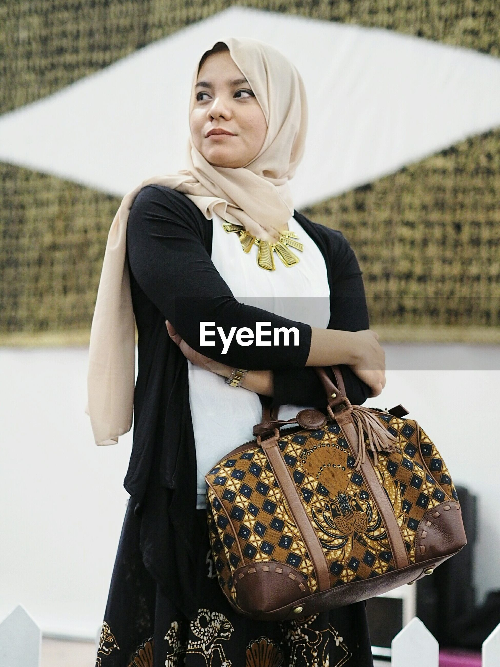 Woman in traditional cloth standing with shoulder bag